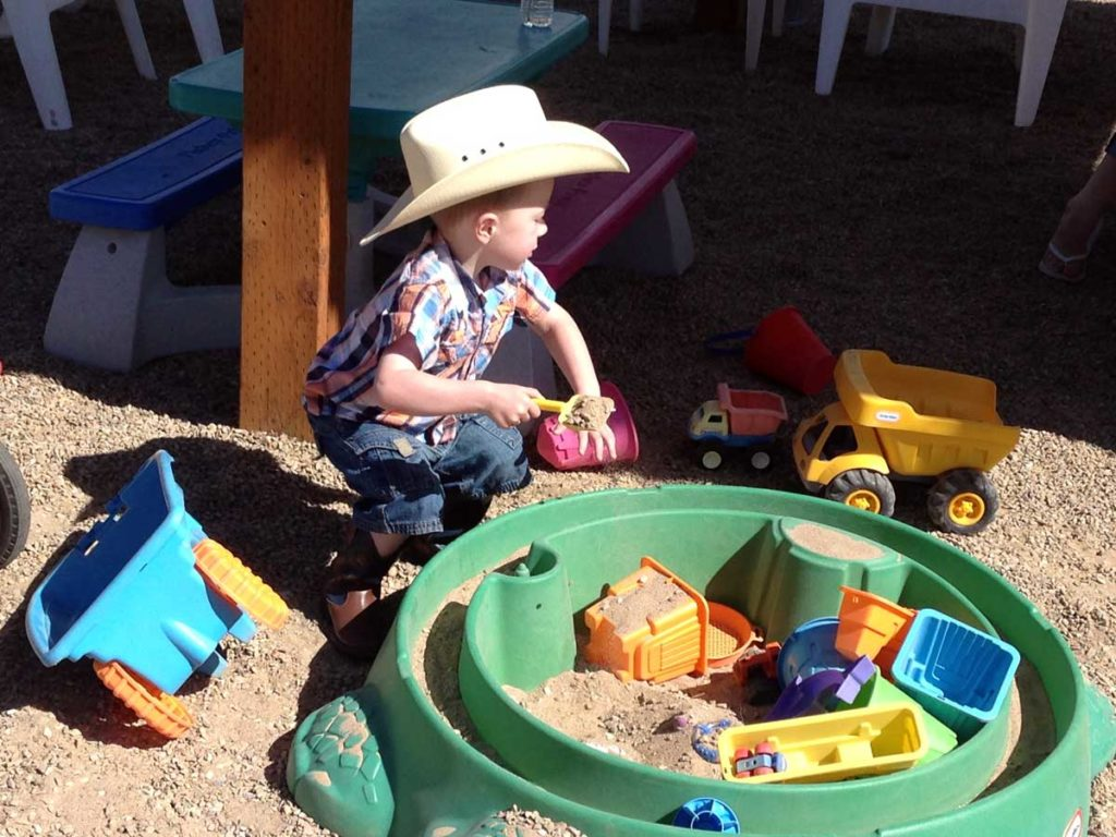 Boy-with-cowboy-hat-in-sandbaox